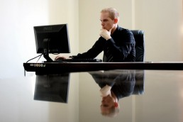 thinking man working and looking on a computer