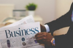 man holding business section of newspaper
